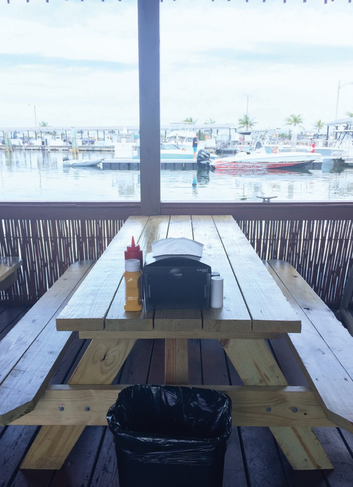 Picnic tables in the Smoked BBQ dining room overlook the Garrison Bight marina.