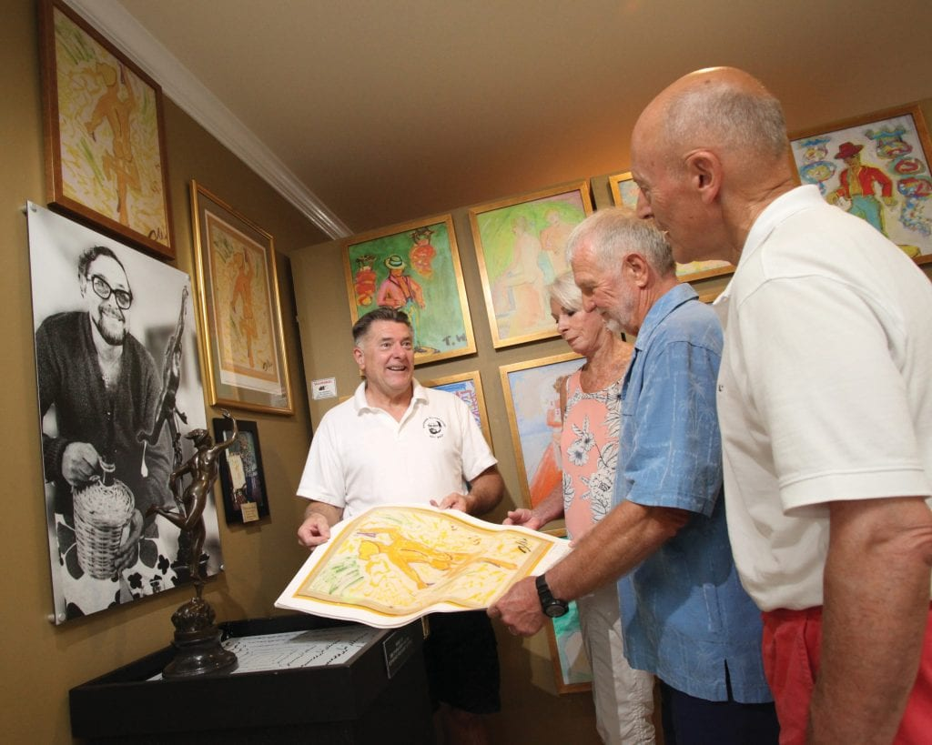 Surrounded by Tennessee Williams memorabilia, Dennis Beaver, left, founder of the Tennessee Williams Exhibit (now Museum) in Key West, shows, left to right, Helen Walker and Leo Waters of Key West and Joseph Vosicky Jr. of Chicago a print of a Williams painting. PHOTO BY CAROL TEDESCO