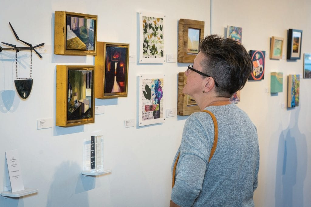 MaryBeth McCulloch admires works at last year's Small Works Show.