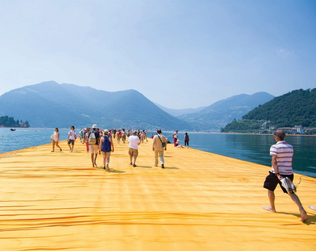"""Part of the dahlia-yellow """"The Floating Piers"""" walkway art installation at Lake Iseo. The documentary film """"Walking on Water,"""" an intimate portrait of installation artist Christo and the stakes of large-scale art, will be presented by Key West Art & Historical Society at the Tropic Cinema on Tuesday, Aug. 13, at 6:30 p.m. PHOTO BY MARCIO DE ASSIS VIA WIKIPEDIA"""