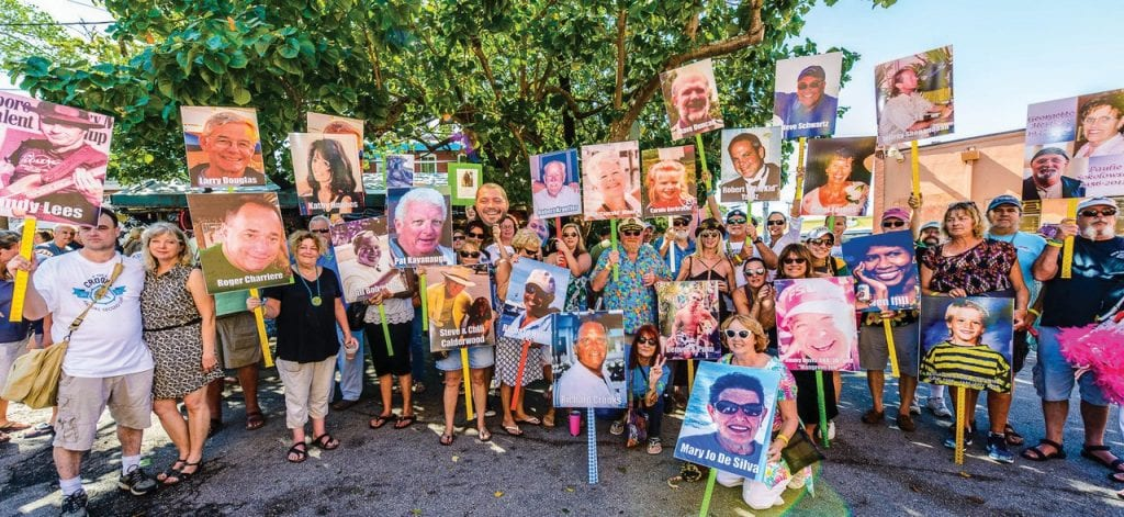 Donors hold up their placards of loved ones for the annual pre-parade group photo during a previous Crooks Annual Second Line celebration.
