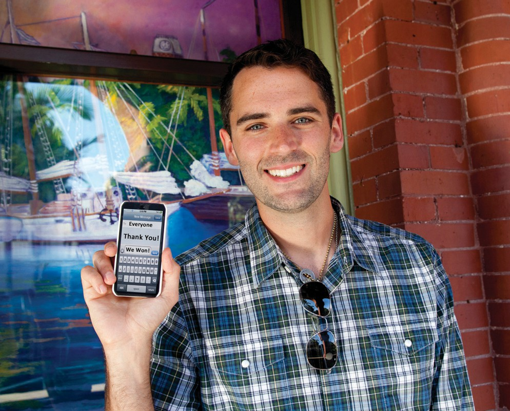 """Key West Art & Historical Society Executive Director Michael Gieda holds up his cell phone in late 2014 with the message, """"To Everyone: Thank You, We Won!"""" The Society received community wide support for a Knight Art People's Choice """"Show Us Your Text"""" campaign, adding an additional $20k to their $15k Knight Arts Challenge Grant to kick-start the inaugural Papio Kinetic Sculpture and Art Bike Parade."""