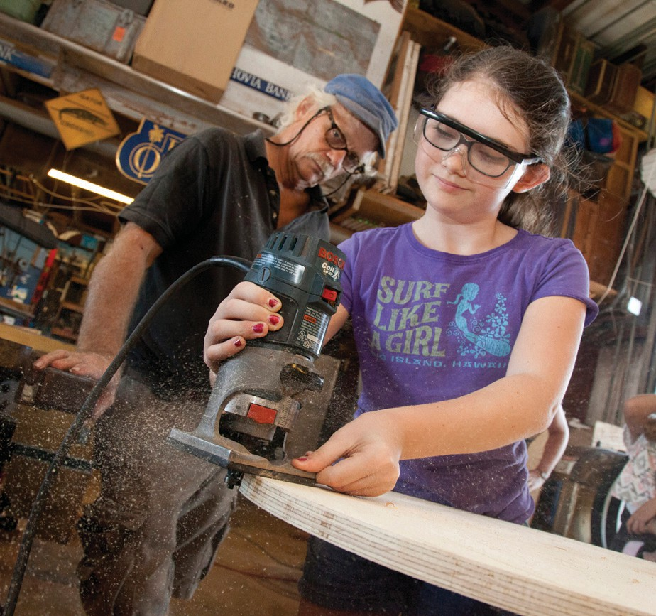 """Every year since its inception, local businesses have sponsored the """"Papio's Pals"""" Kinetic Coaches in Schools education program. Here, Sadie Dodds wields a router in Jimmy Wray's Stock Island workshop while working on Horace O'Bryant School's 2016 entry."""
