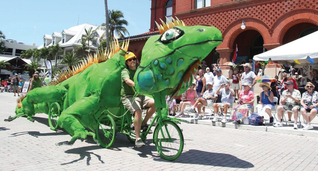 """Cayman Smith-Martin pedals his Rebel Yell Award-winning """"Iguana,"""" made from mostly recycled materials, past the Custom House Museum in the 2019 Parade."""