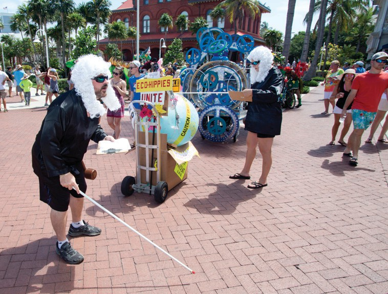 """""""Blind"""" judges Gabriel Price, left, and Alison Higgins, right, peruse parade entries in the line-up area behind the Custom House Museum before the 2019 Papio Kinetic Sculpture and Art Bike Parade."""