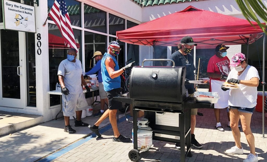 Neighbors helping neighbors; serving up free burgers and hot dogs in the Gary the Carpenter parking lot for those in need.