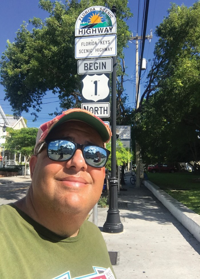 Miami-based TV producer and humanitarian Chris Sloan at the end of U.S. 1 during his visit to Key West. COURTESY PHOTO
