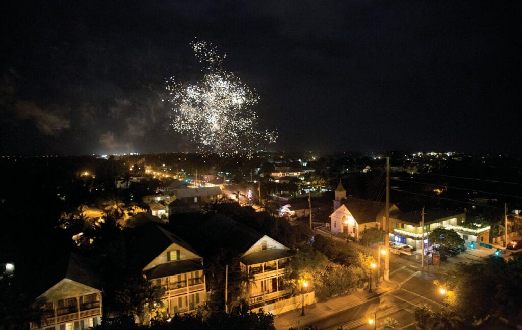 "Individual lights and fireworks, viewed from the 86-foot-high observation deck of the Key West Lighthouse, light up the sky over Key West's Old Town district at midnight on Dec. 31. Though Key West observed a 10 p.m. curfew over New Year's weekend to help curtail COVID-19 transmission, locals and visitors were invited to participate in an ""Illuminate Key West"" virtual event that included a Florida Keys Media radio simulcast countdown broadcast from the Lighthouse grounds and invited one and all to shine individual lights into the sky at midnight to welcome the New Year."