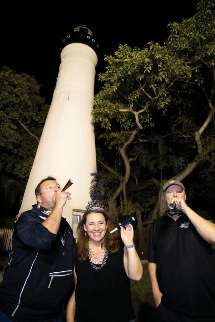 "Florida Keys Media general manager Rick Lopez (left), radio host Bill Hoebee (right) and ""We've Got the Keys"" owner and event director Nadene Grossman Orr (center) ring in the New Year on the grounds of the Key West Lighthouse. Grossman Orr designed the Illuminate Key West event to bring the pandemiccaused socially distanced community together via light and sound. Photos by Carol Tedesco"