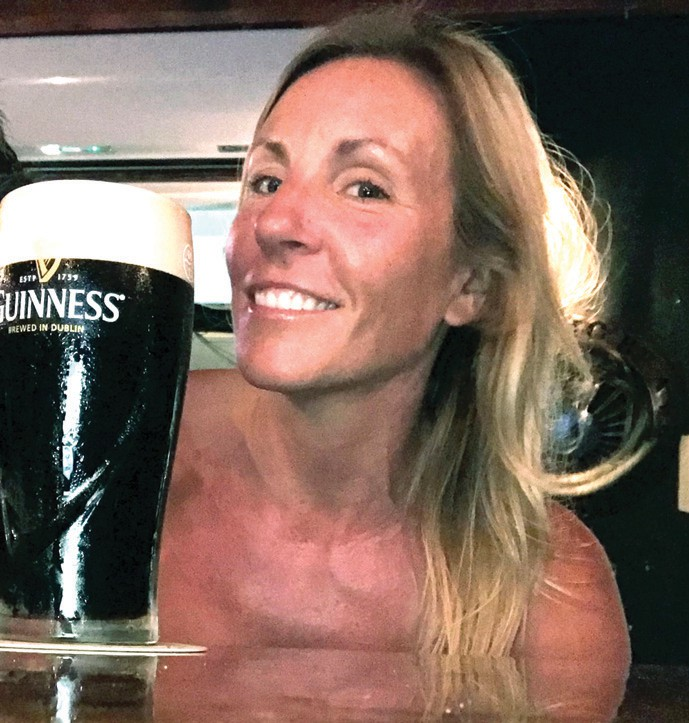 """Sharla Sharkey raises a pint of Guinness, but acknowledges that her drink of choice is nonalcoholic — """"I only stay hydrated with water,"""" she says. COURTESY PHOTO"""